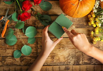 Florist at work. Pumpkin, oasis and tools on wooden background, top view