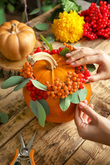 Florist at work. Composition with pumpkin, rowan and viburnum on wooden background