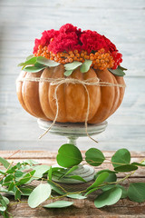 Pumpkin with flowers and berries on blurred background
