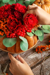 Florist at work. Home decoration with pumpkin, flowers and berries on wooden background
