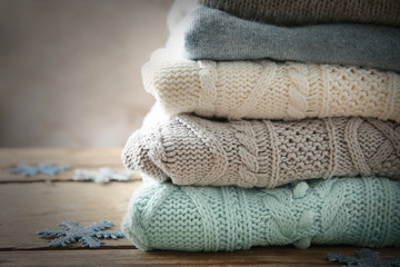 Stack of woolen clothes on wooden table, closeup
