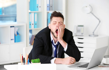 Yawning tired business man sitting at workplace in office