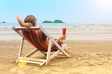Young woman in deck chair is sitting at sea beach with glass of juice or cocktail and relaxing. Luxury vacation in Thailand.