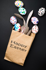 Easter bunny in a paper bag. Rabbit. Black background. Easter ideas. Easter eggs. Space for text. Black lettering happy easter.