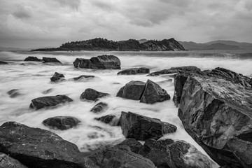 A black and white rocky ocean coastline over the south China sea in the bay of Vung Lam Bay Vietnam.
