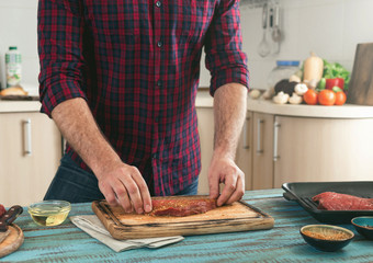 Man preparing grilled steak on the home kitchen
