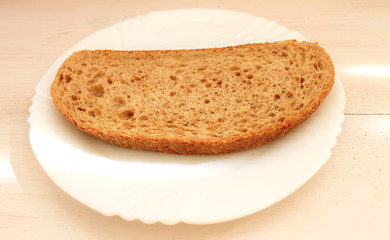 Slice of dark bread with bran on the white plate