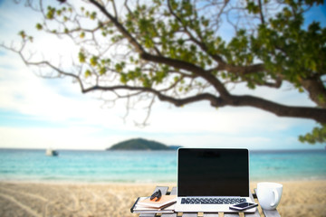 Front view of cup and laptop on table in Office park and blurred background of the beach in the summer, Similan, Thailand