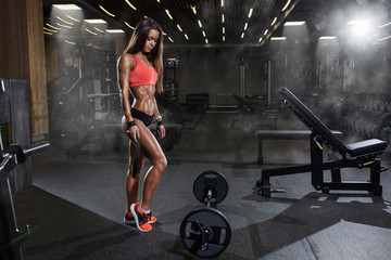 Sexual young woman with a perfect body is preparing for the exercises with barbell in gym