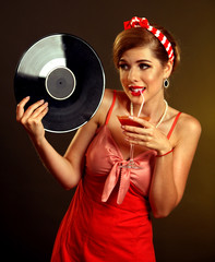 Retro woman with music vinyl record. Pin up girl drink martini cocktail . Pin-up retro female style. Girl wearing red dress drinking beverage through straw and is lost in thought.