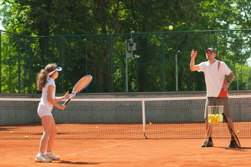 Tennis instructor with young girl