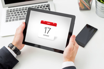 Businessman holding tablet with calendar on screen