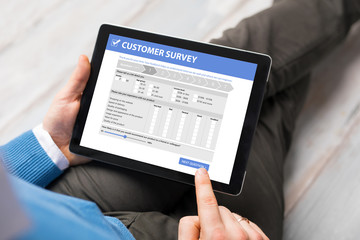 Man filling customer survey form on tablet computer