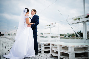 Wedding couple stay on the pier berth at cloudy day.