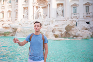 Happy man trowing coins at Trevi Fountain, Rome, Italy for good luck. Caucasian guy making a wish to come back.