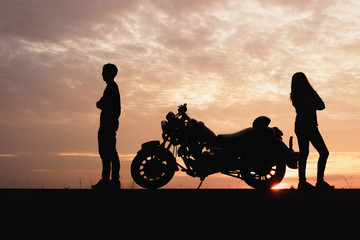 Silhouette of couple are quarrel with a motorcycle at sunset background.