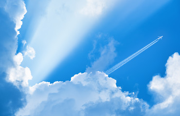 Wall Mural - Airplane flying in the blue sky among clouds and sunlight