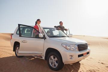 Couple standing on a car door on desert
