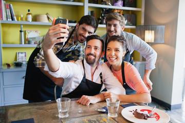 Chefs taking selfie using mobile camera.