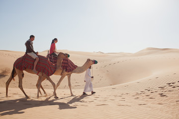 Couple riding on camel at desert.