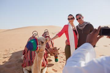 Arab man photographing couple at desert.