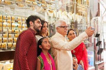 Man taking selfie with family at jewelry shop using mobile camera.