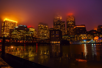 Fotobehang - View of Boston skyscrapers night.  The tops of the buildings in the fog and haze. Rainy foggy weather, brilliant paving and lights of skyscrapers.