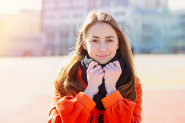 Beautiful young woman in orange coat walking in the city