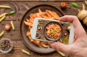 Man hand takes photo of penne with tomato sauce and fresh basil by smartphone