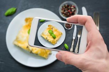 Hand takes shot of fresh lasagna with bechamel sauce with mobile phone