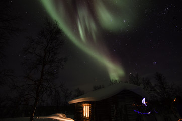 Northern lights over the cottage in lapland landscape in Finland