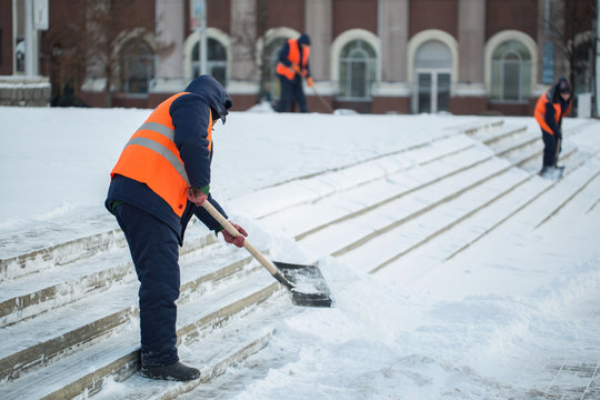 Workers sweep snow from road in winter, Cleaning road from snow storm.