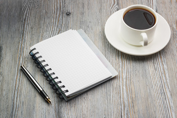 Notebook with pen on an old rustic table. with coffee cup