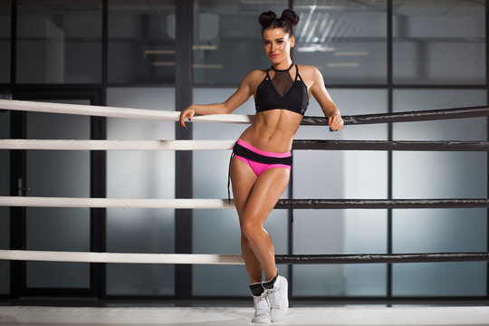 The woman in the ring in an office building. Pink shorts, white sneakers