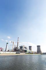 modern power plant near river in blue sky
