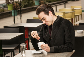 one young man looking at coffee cup