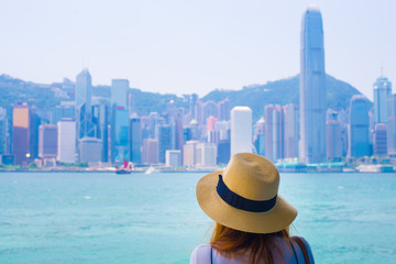 Woman tourist is watching view of Victoria harbor in Hong Kong.
