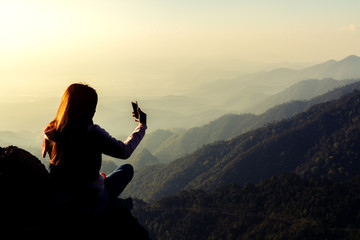 silhouette women sitting and use smartphone selfie on mountain