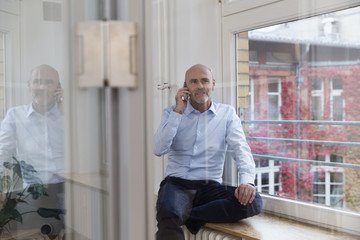 Businessman on cell phone at the window
