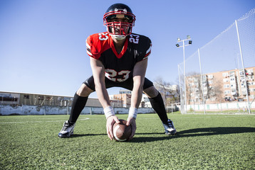 American football player with ball on sports field