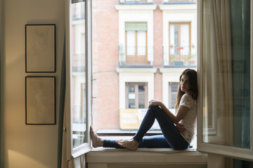 Woman sitting on window sill at open window