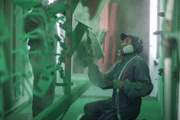 Painters spraying steel components in spray booth of factory