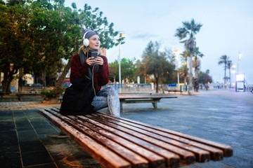 Young woman sitting on a bench listening to music with a smartphone