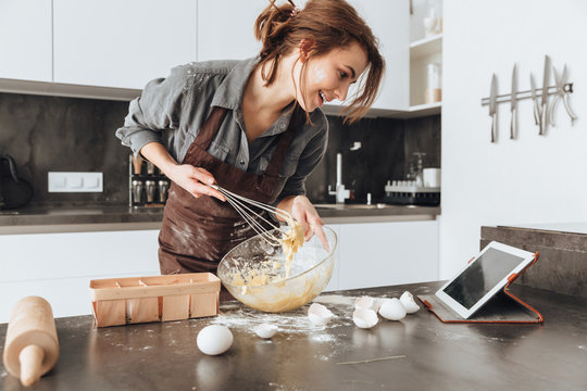 Cheerful woman cooking and looking at tablet computer.