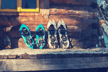 Snowshoes are on the porch of an old log cabin. Close up