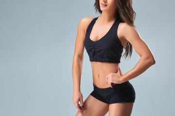 Slim woman's body over grey background