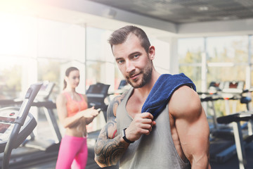 Young athletic man in gym, lifestyle portrait in fitness center