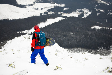 extreme free skier with safety helmet and avalanche backpack holding splitboard in cold winter mountains