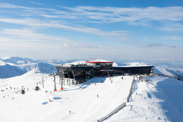 modern cableway skiing resort in austrian alps with skiers and snowboarders on blue sky mountain peak
