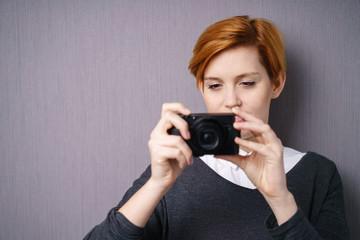 frau hält eine digitalkamera in den händen und schaut auf den display
